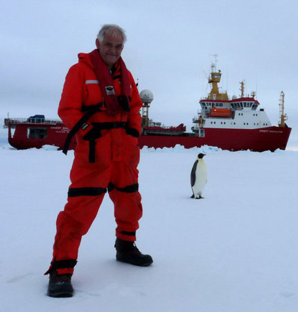 Photo of David Meldrum in Antarctica with two penguins and the research vessel in the background