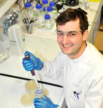 PhD student Guy Trimby pipetting sample in laboratory wearing laboratory clothing