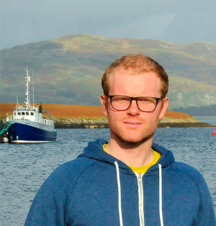 Head and shoulder shot of physical oceanographer Neil Fraser outside with research vessel behind