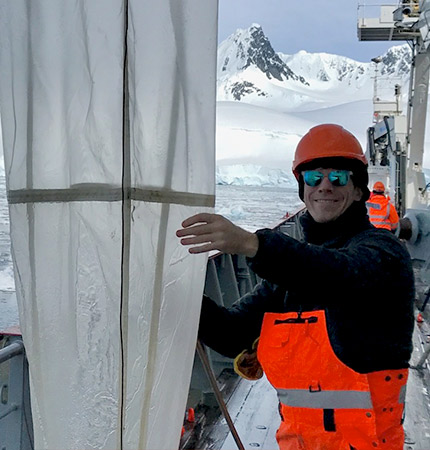 Dr Will Goodall-Copestake cleaning a net in the Arctic