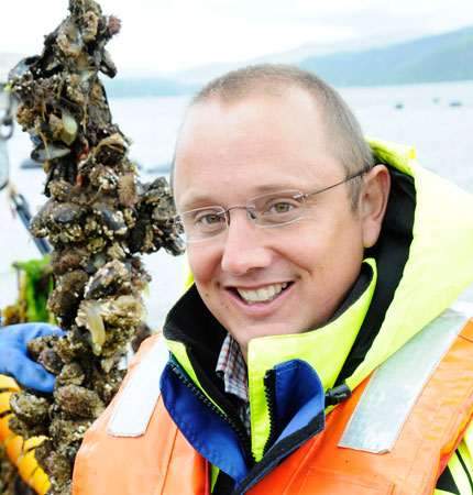 Adam Hughes on a marine farm with rope-grown mussels in the background