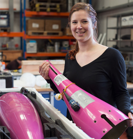 Physical oceanographer Marie Porter with a pink seaglider opened up for technology check