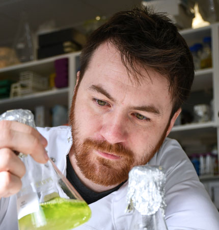Head and shoulder photo of Mikey Ross in a white lab coat with a flask full of algae