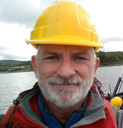 Callum Whyte on a research vessel with hard hat