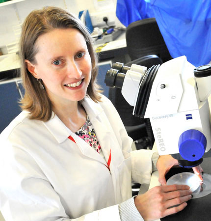 Rachel Allen wearing white lab coat working on a microscope