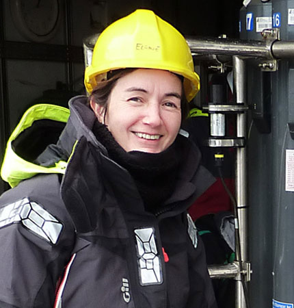 Support scientist Sharon McNeill next to water collecting equipment on oceanographic fieldwork