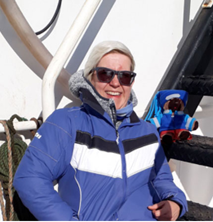 A smiling Elaine Mitchell relaxing aboard a research vessel donning Arctic clothing