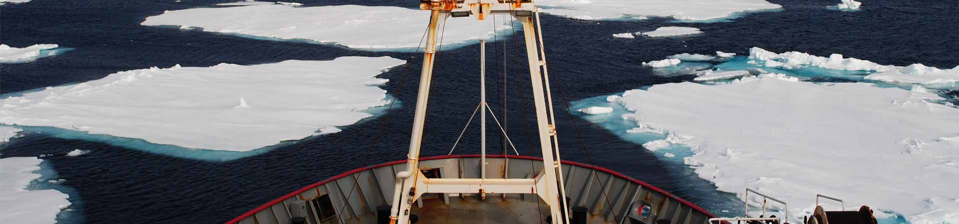 View from bow of a research vessel sailing though Arctic Ocean with sea ice
