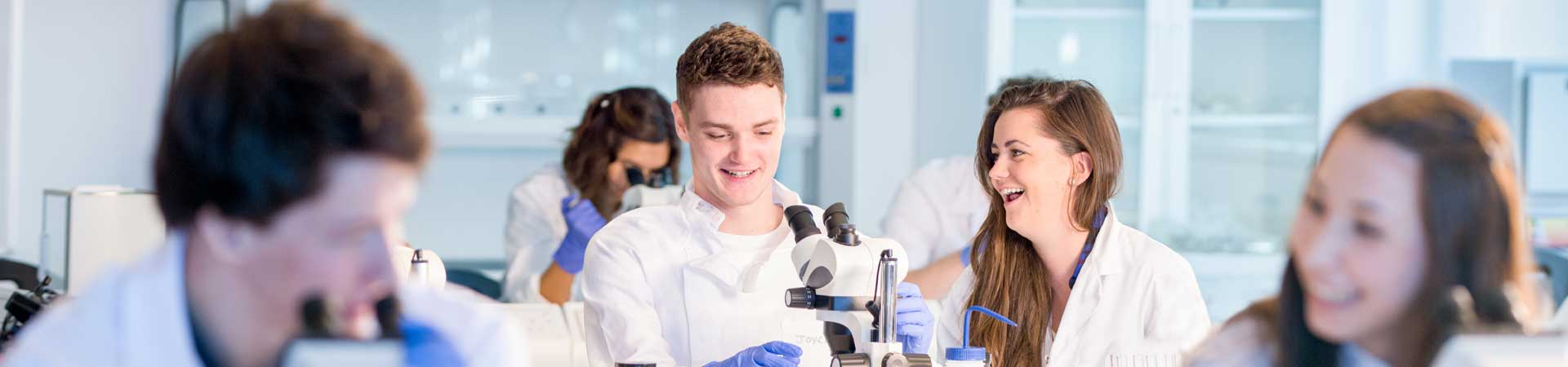 This picture shows a row on marine science students in lab coats in a teaching laboratory having fun with microscopes