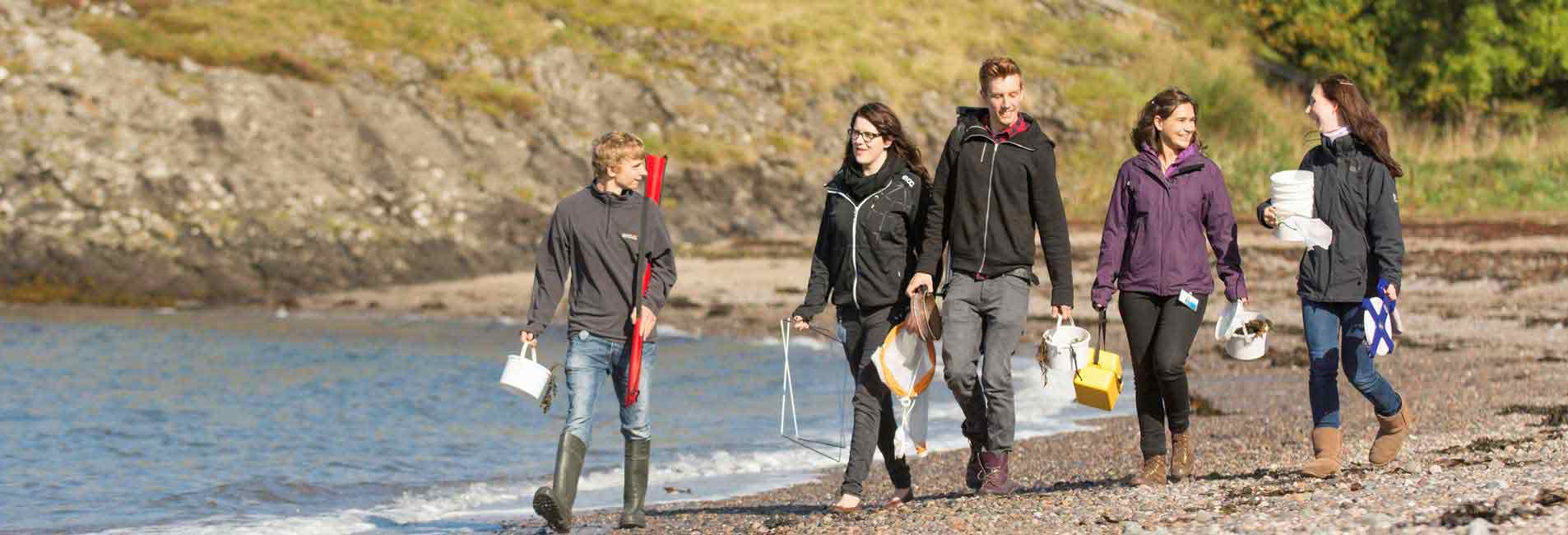 The picture shows a group of fresh-faced marine science undergraduate students walking on the beach with some of their fieldwork equipment