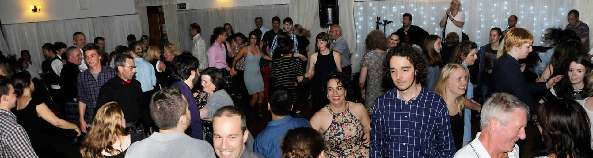 Picture showing very happy crowd of students with their friends, families and lecturers during the graduation ceilidh in the Argyllshire Gathering