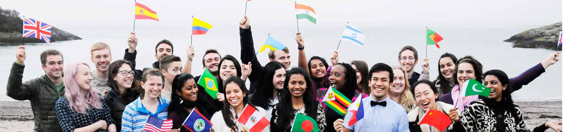 A group of international students waving flags showing their nationalities.