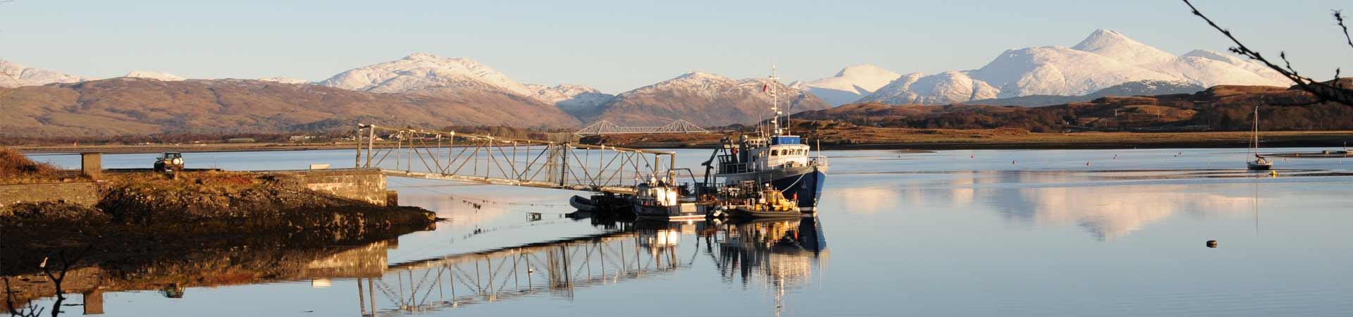 Research vessels moored on SAMS pontoon with crisp mountains in background