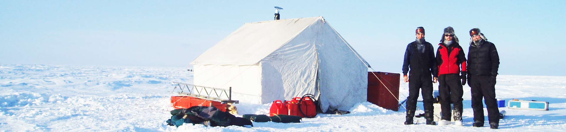Photo of group of researchers outside a tent in the polar regions, ready to go sampling