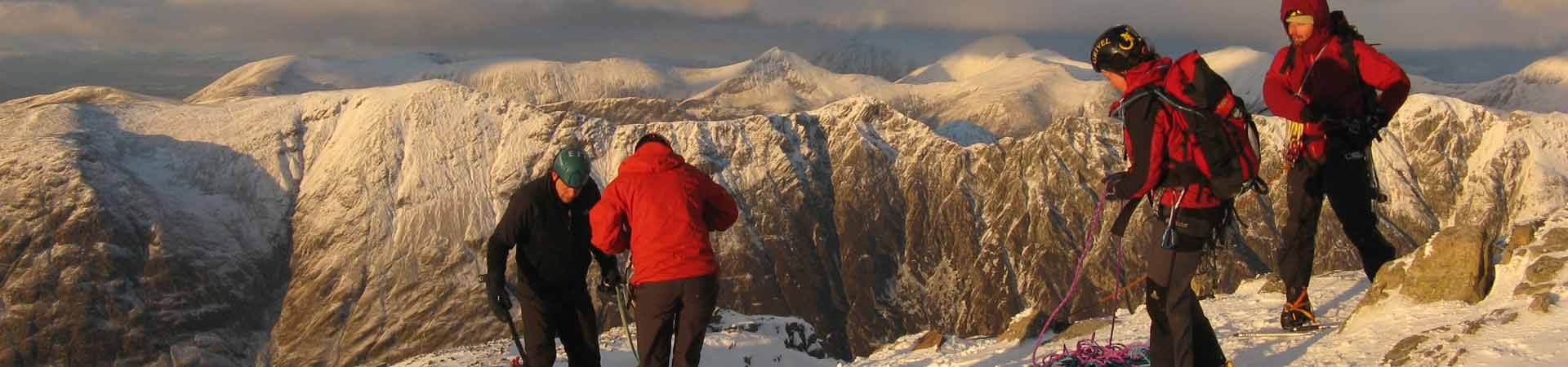 Four students mountaineering in the Scottish Highlands during winter with snow covered mountains behind them.