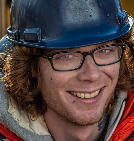 Photo showing a smiling Dr Jordan Grigor wearing a hard hat