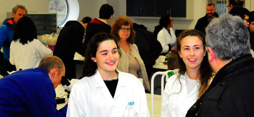 Photo showing a parent talking to two current students in lab coats while in the background others look through microscopes etc