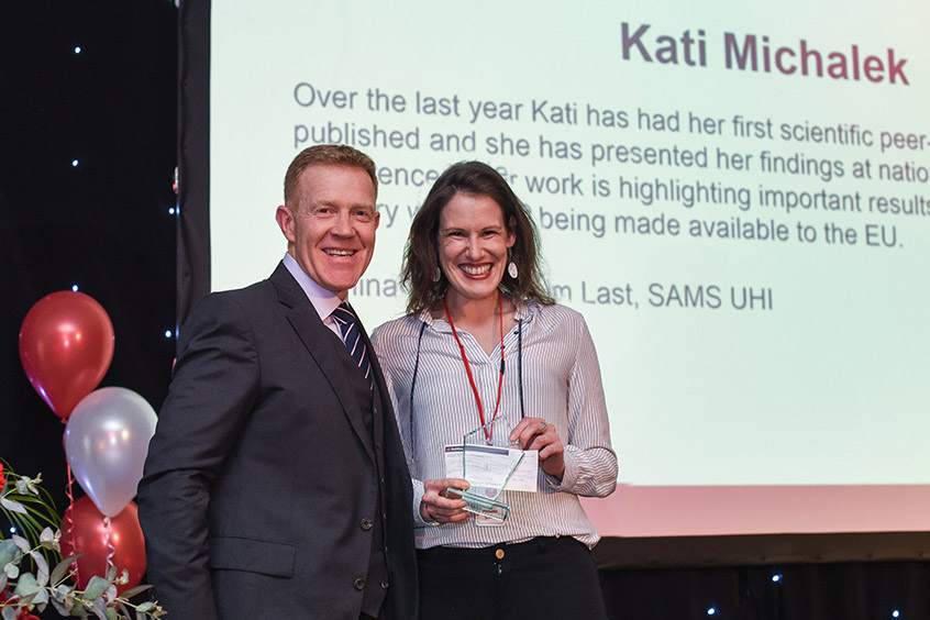 Farmer and BBC presenter Adam Henson presents SAMS UHI PhD student Kati Michalek with her Higher Education Learner of the Year prize