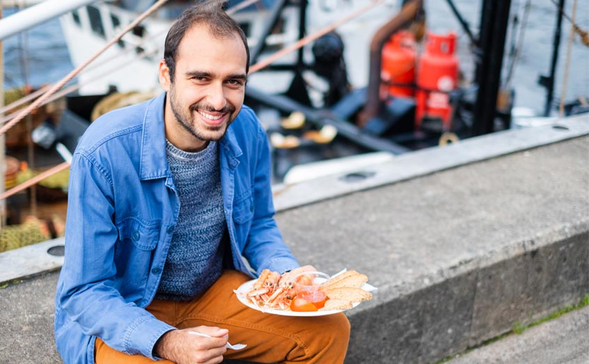 RiseUp project researcher George Charalambides, SAMS, is pictured at the Railway Pier in Oban, one of many UK towns that benefits from a thriving seafood sector.